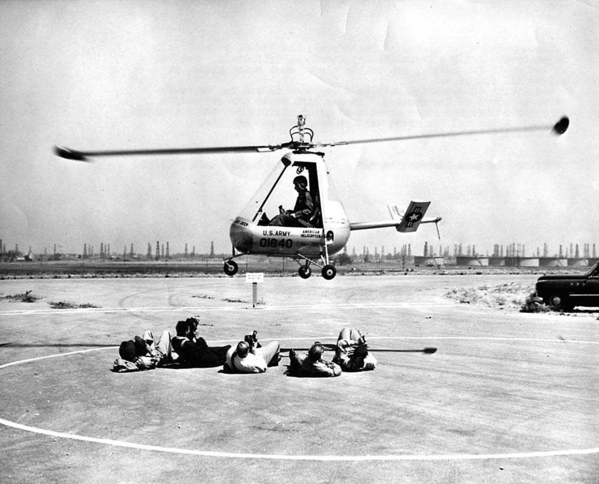 Luftfoto. Ett helikopter i luften like over bakken, American Helicopter XH-26. Fem personer ligger på bakken under helikoptret.