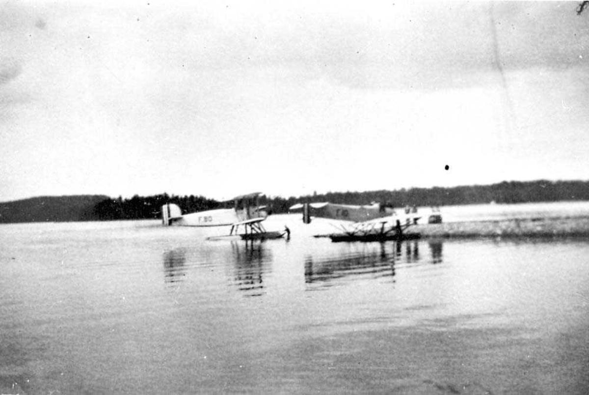 To fly som ligger ved en kai, Douglas DT-2B/DT-2C og Hansa Brandenburger. Flere personer ved flyene.