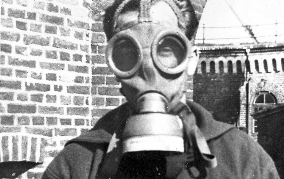 Portrett. En person, mann i gassmaske.