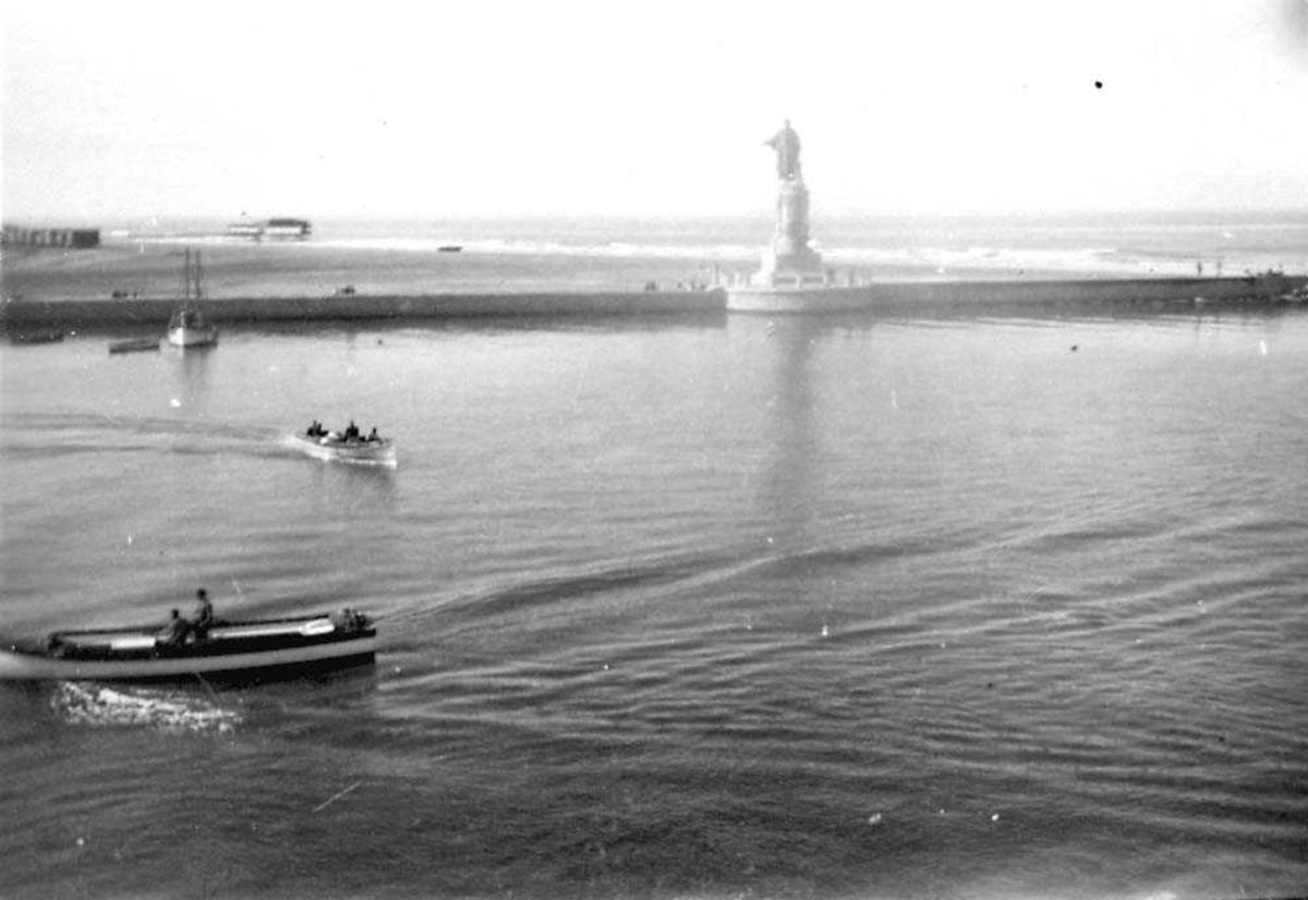 En statue som står på en molo. Flere båter i forgrunnen.