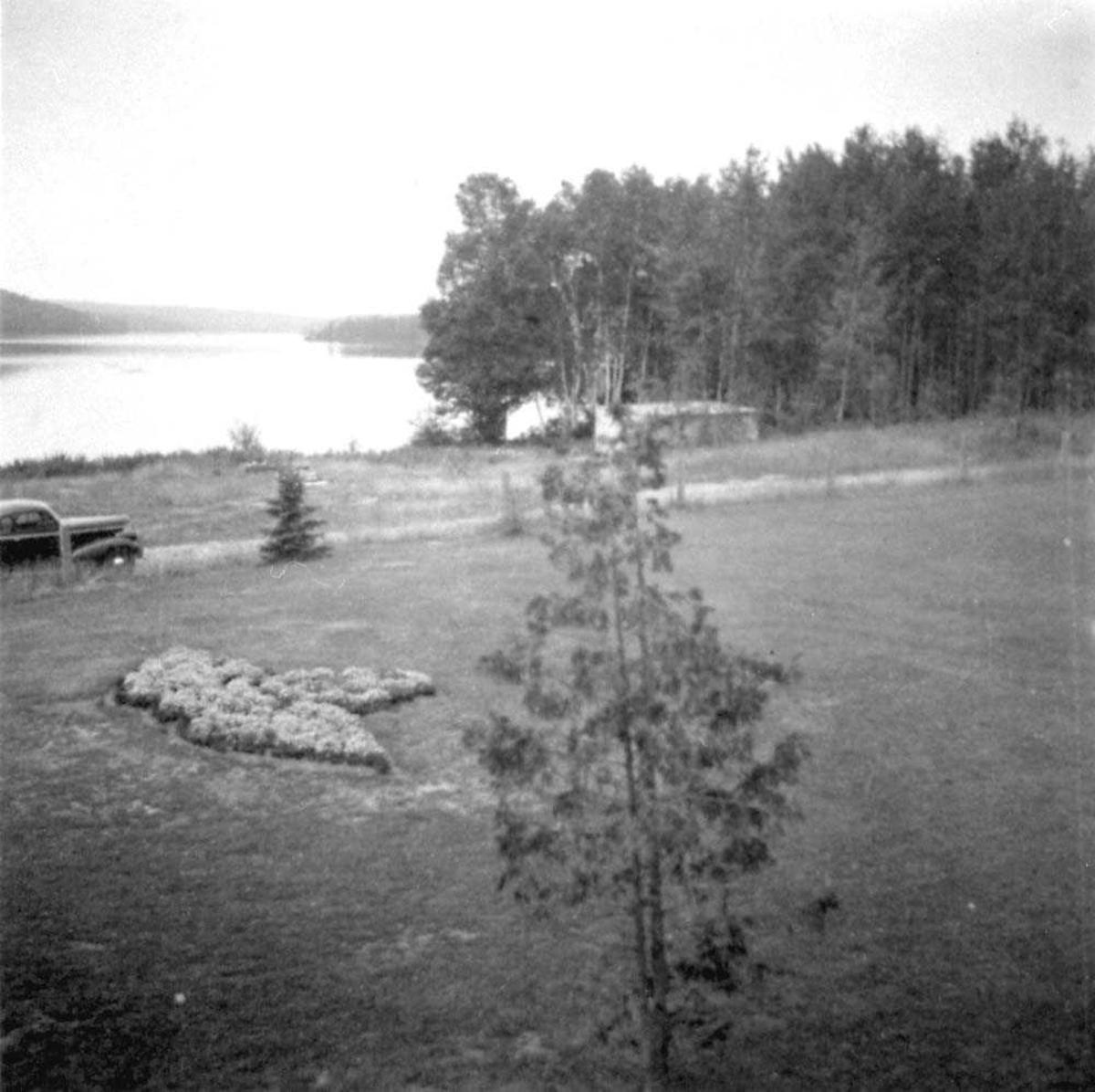 Åpen plass med vann og skog i bakgrunnen.