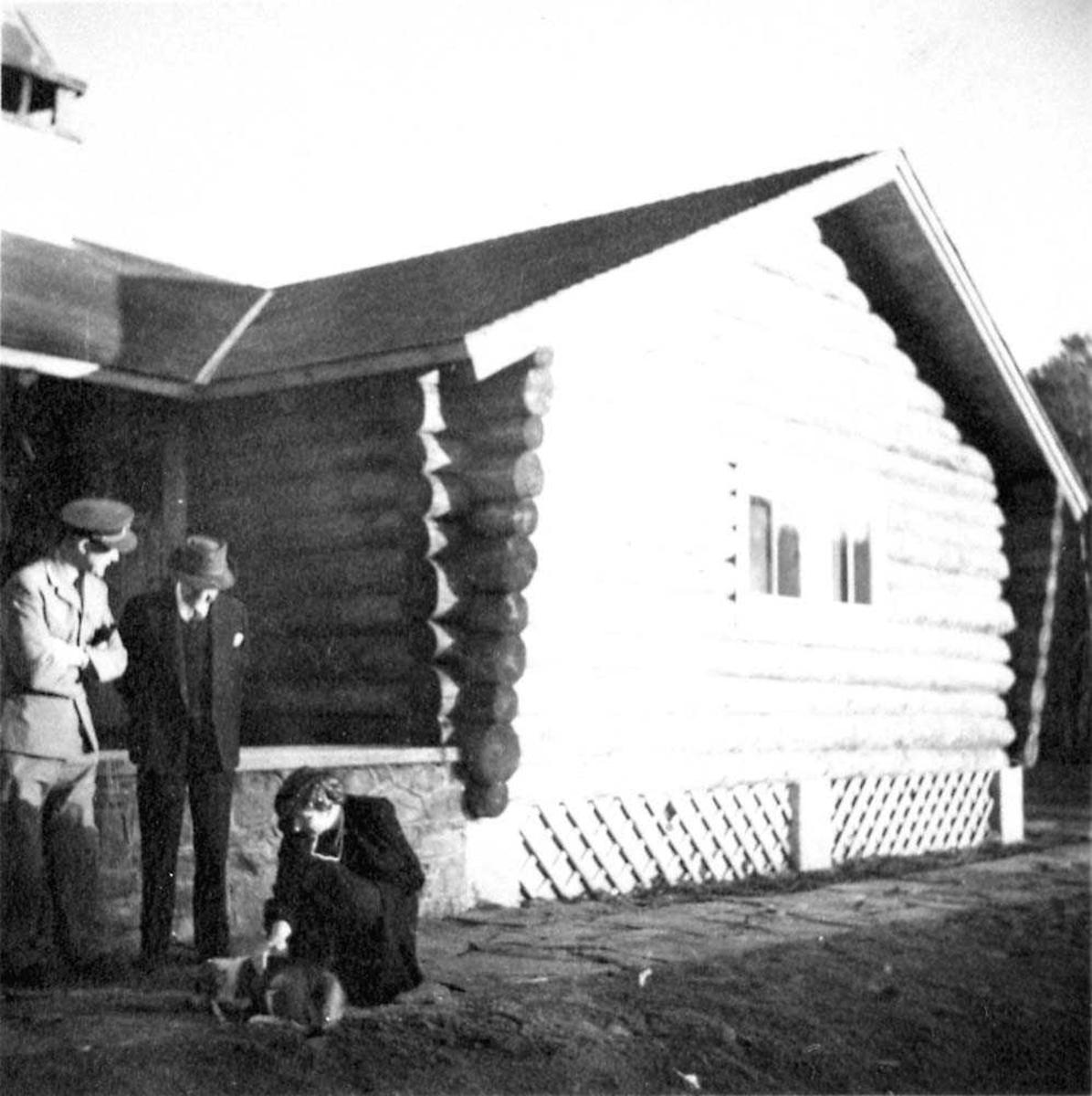 Portrett. Tre personer, to menn og en kvinne foran en bygning. Kvinnen klapper en hund.