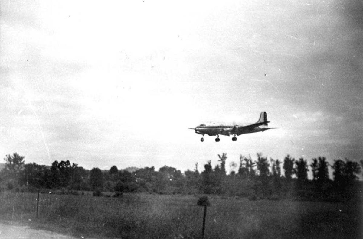 Luftfoto. Ett fly i luften, like før landing.