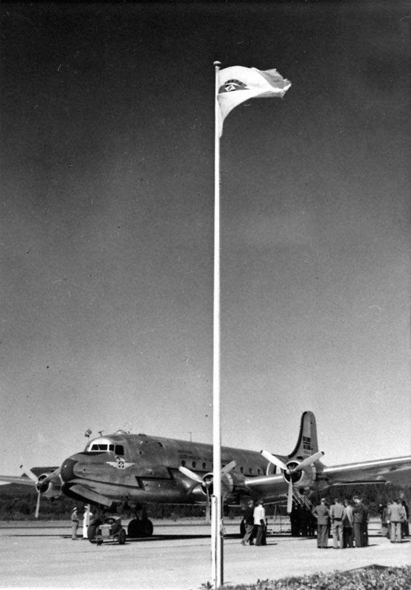 """Ett fly på bakken. Douglas DC-4/C-54 """"Norse Comander"""" LN-PAW fra Braathens SAFE. Flere personer rundt flyet. Flaggstang med Braathens SAFE flagg i forgrunnen."""