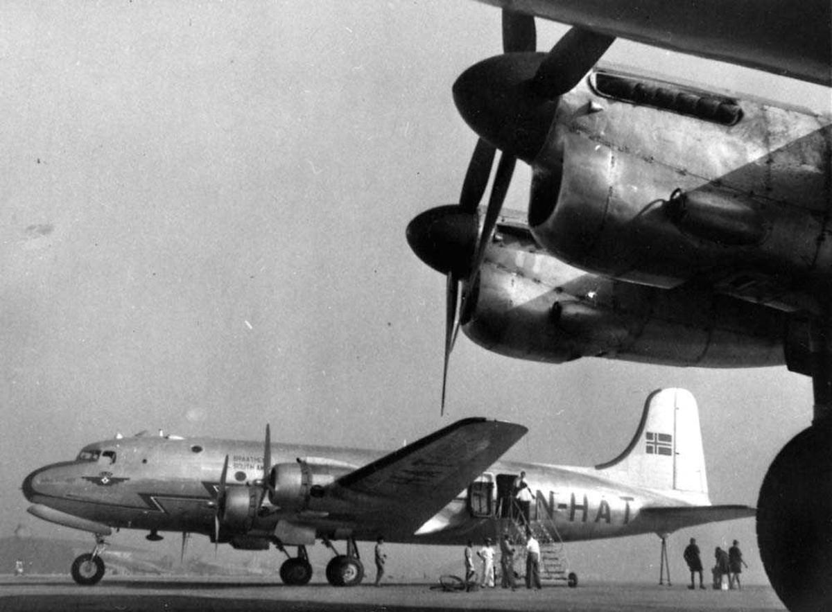 """Lufthavn. Ett fly på bakken. Douglas DC-4/C-54 """"Norse Skyfarer"""" LN-HAT fra Braathens SAFE. Flere personer ved flyet. Motorene til et annet fly i forgrunnen."""