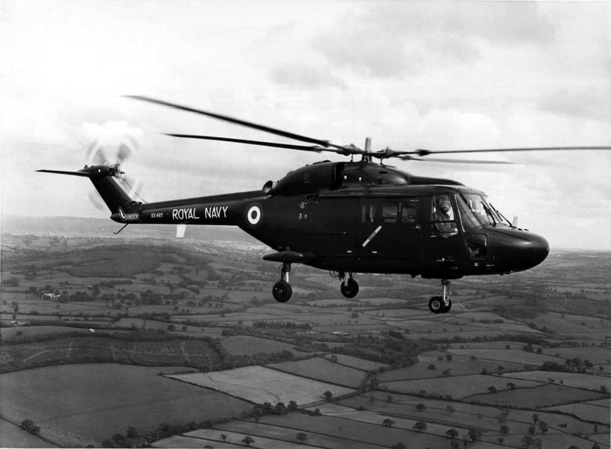 Ett helikopter i luften over dyrket mark. Westland Lynx HAS2 tilhørende Royal Navy merket XX469. Pilot ses i cockpit.