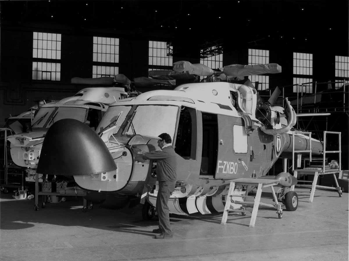 Tre helikoptere på bakken, under arbeid. Westland Lynx HAS Mk.2. merket F-ZKBO. Tekniker ses arbeidene på helikopteret i forkant.