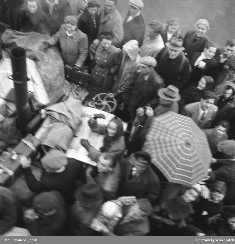 Ekspedisjonsprammen med passasjerer fra/til hurtigrute ved kai i Berlevåg. Bildet er tatt fra kaia ned mot båten. Passaserene står ombord og er på godt humør, en del av dem ser rett på kamera og smiler.  Et paraply er slått opp for å beskytte for regnvær.