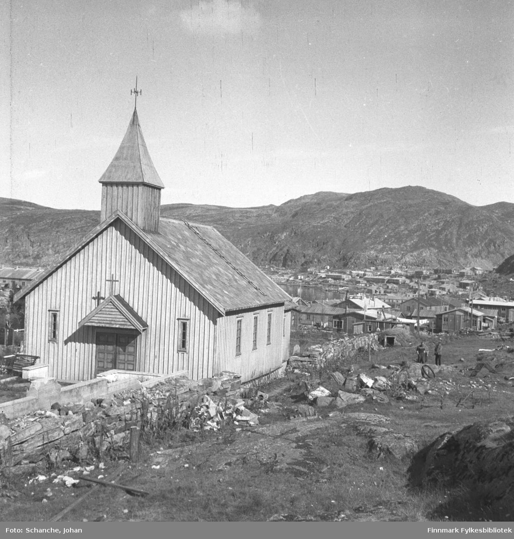 Kapell i Hammerfest fotografert i sommer -46. 'Bare gravkapellet sto igjen etter ødeleggelsen' står det i negativposen. Brakker og andre nybygg skimtes på bakgrunnen.