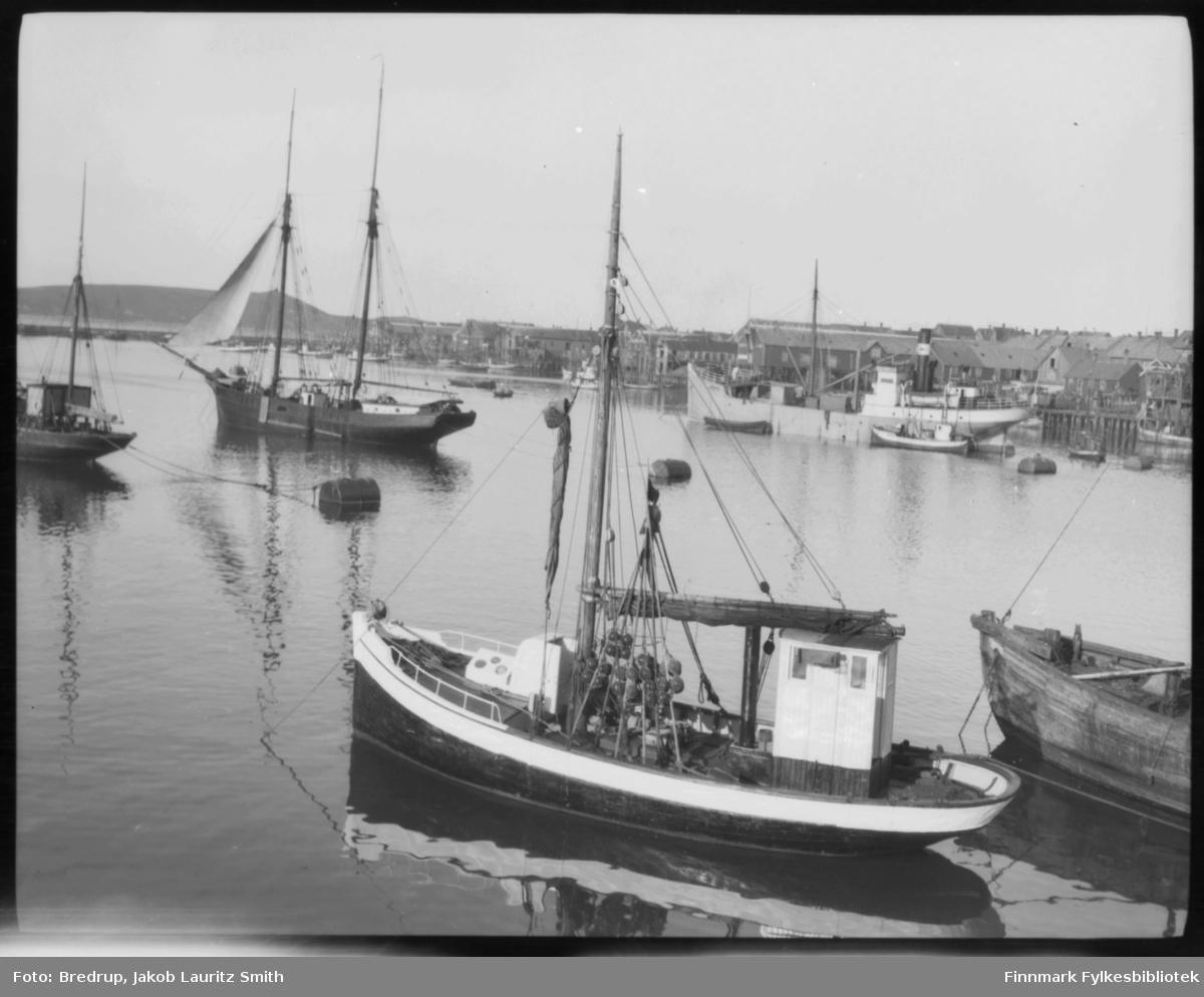 Bilde fra havna i Vardø..  Havet er blikkstille, og små fiskebåter og større fartøyer i massevis ligger forankret.  Vi ser kaier, fiskebruk og pakkhus og moloen i bakgrunnen. Bildet viser en større seilbåt, et dampskip, en sjark.