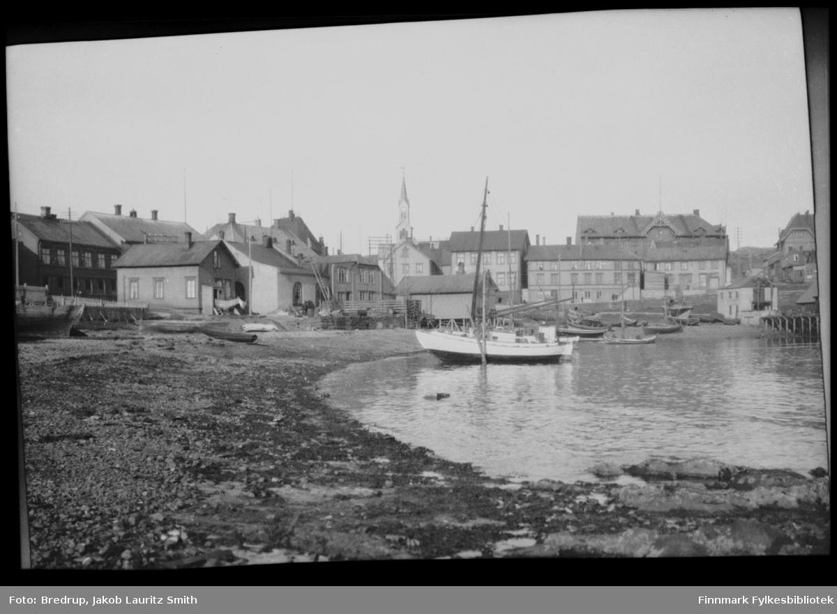 Båter trukket opp i fjæra, Valen i Vardø.  Bildet viser flere bygninger i nærheten, noen er boliger.  Kirka i bakgrunnen.