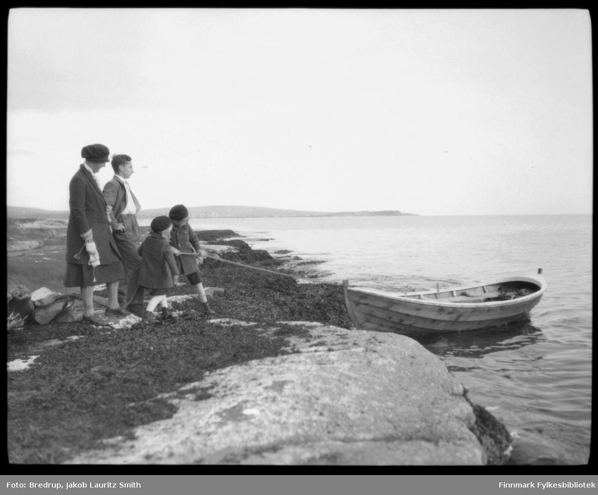 En familie med to barn fortøyer en robåt, antakelig på Vadsøya.  Kvinnen er Hildur Bredrup. Barna er Trygve Bredrup, og antakelig Rith Bredrup Handal.  Vi antar det er Ruth, pga aldersforsskjellen.  Mannen er ukjent, Hildur Bredrups bror?