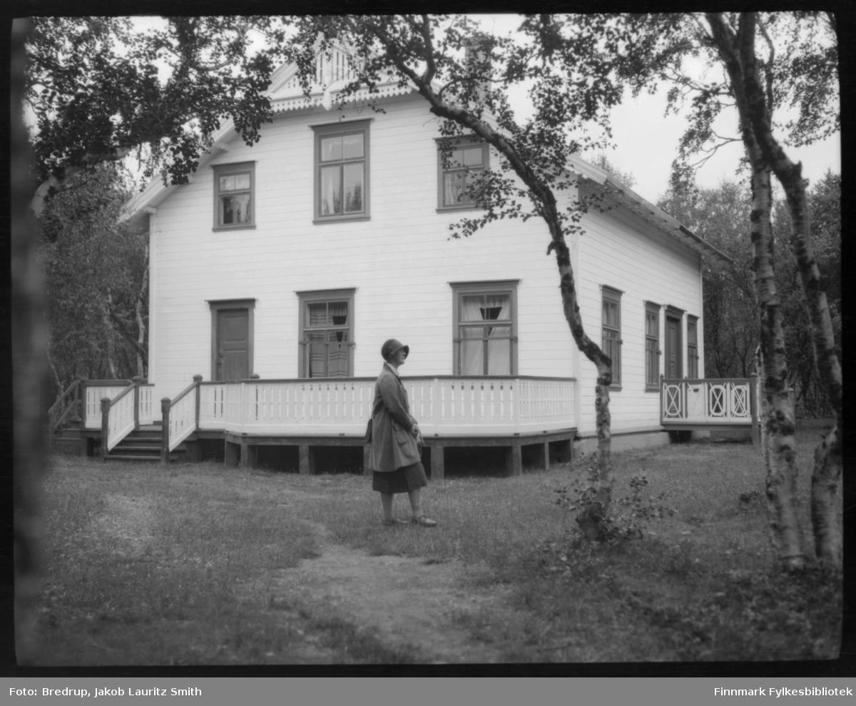 Hildur Bredrup fotografert foran et stort, lyst hus, omgitt av høye trær.  Hun er kledd i drakt og hatt.  Er huset det samme som på Fb.98012-213?  Huset er omgitt av en stor veranda.