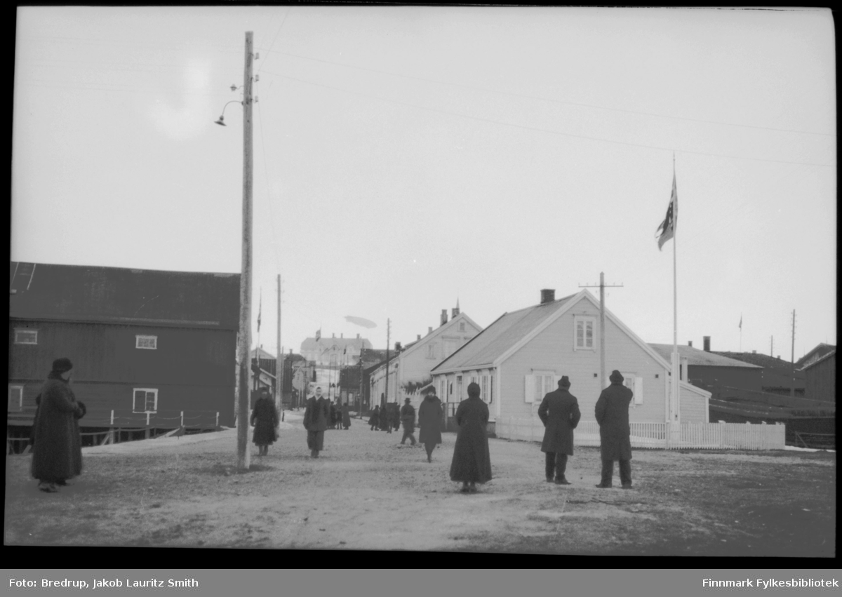 Bildet er tatt nederst i Tollbodgaten.  Et luftskip svever over Amtmannsgården.  Det er spredte tilskuere i gata.  Antakelig er dette bildet tatt under 'Norge's mellomlanding i Vadsø 1926.  Det er mye snø i gatene fortsatt, og hele byen flagger.