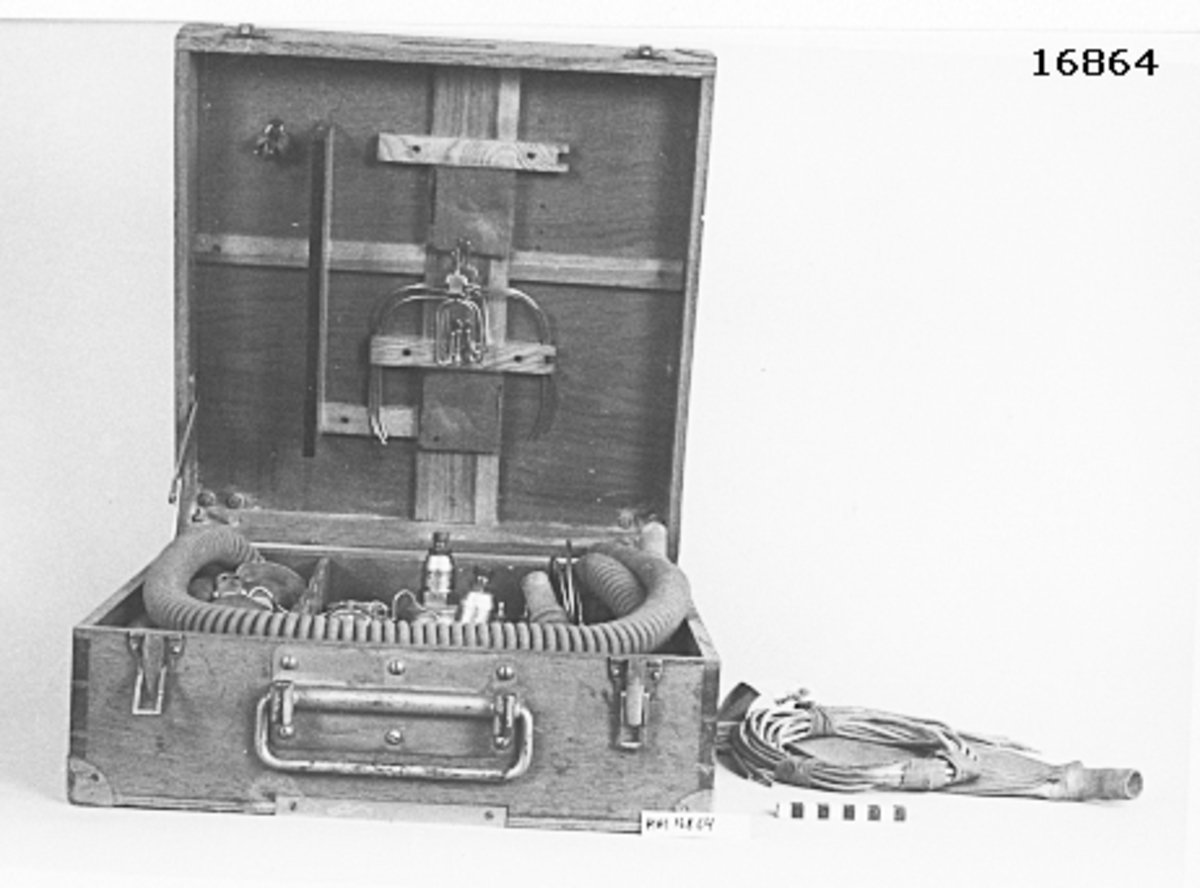 Låda av fernissat trä, försedd med lock på gångjärn och låsöverfall samt rörligt handtag i vitmetall på framsidan. Metallförstärkta hörn. Inuti lådan finns följande föremål: 2 st manometrar, 4 st andningsslangar textilklädd gummislang (L= 125 mm D= 33 mm samt 2 st små: L= 210 mm). 4 st munstycke för upphängning, 4 st metallföremål för upphängning, 2 st tredelade kopplingsrör i metall, 1 st metallbygel med skruv, 2 st byglar för hålla mask mot ansikte, 1 st nyckel passande till tre muttrar av olika storlek, 6 st gummislang (L= 1500 mm D= 4 mm), 1 st gummilunga.