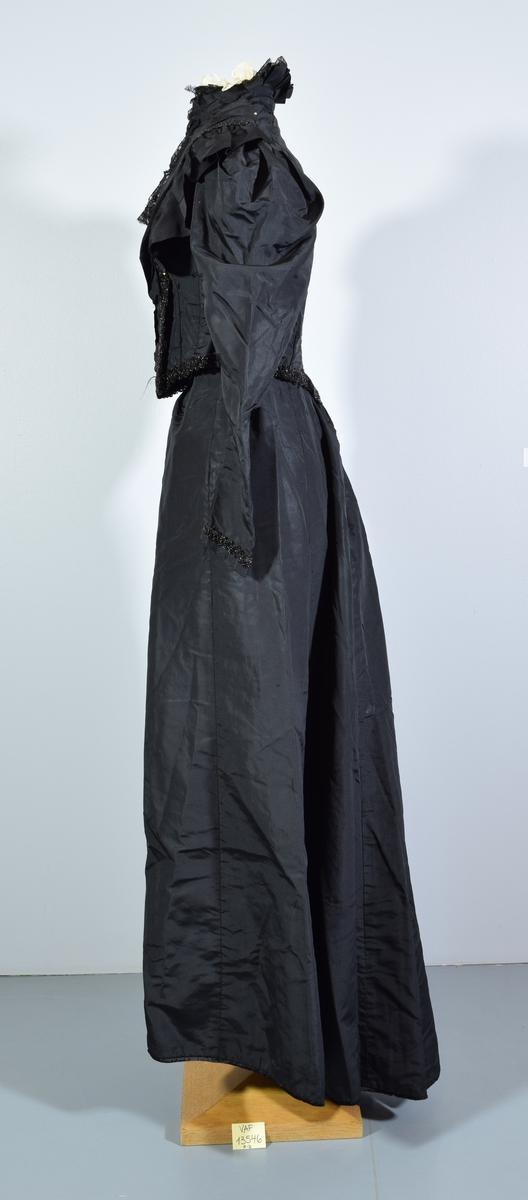 Todelt svart brudekjole bestående av langt glatt skjørt (b) og kort svart jakke/overdel (a). Jakka har forstykke dekorert med svarte perler og blonder, den festes med metallhekter på venstre side av overdelen. Jakka har en krage/høy hals med bølgete kant, ett lag svarte blonder og ett lag hvitt tynt nettingaktig stoff. Ermene er dekorert med en bord med svarte perler nederst. Nederst på jakka rundt midtjen er det også en bord med svarte perler. Overdel og skjørt festes sammen ved hjelp av tre metallhekter.