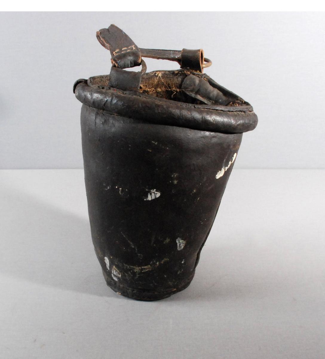 Brannbøtte i lær med lærhemper for hank. Hanken er av lær og forsynt med metallringer som er tredd inn på hempene.