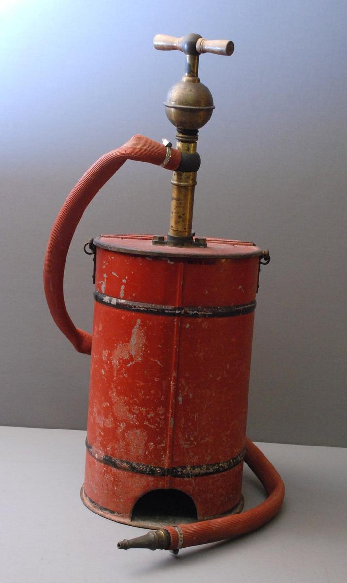Sylindrisk spann med hank. Pumpe ned i spannet med pumpehåndtaket på toppen, der også slangen med munnstykke er festet. Hengslet lokk på toppen kan åpnes. Malt skjold på beholderen.