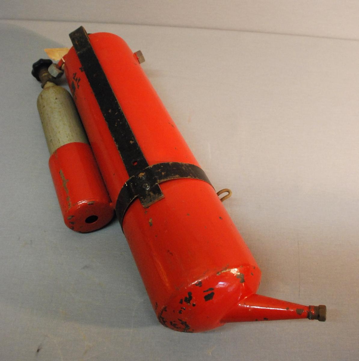 Sylinderformet brannslokkingsapparat med ventil på toppen. Veggbrakett festet med metallbånd rundt sylinderen. Utløp i bunnen av apparatet. Holder for drivgass festet på sylinderen. Oppi holderen er det en sylinderformet sylinder for kullsyre-drivgass. Drivgassylinderen har ventilratt på toppen og forbindelse til apparatet.