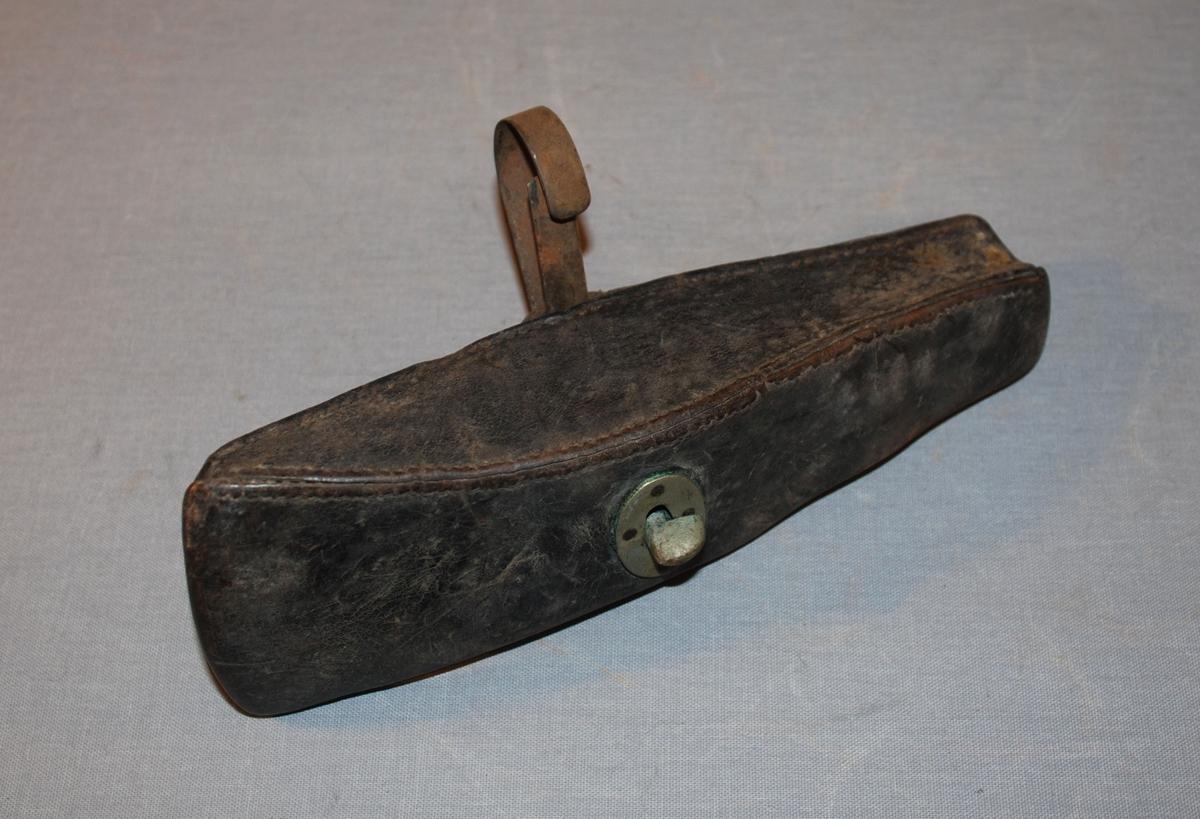 Futteral til brannøks. Futteralet er sydd i skinn og har form som et øksehode. Lukkes med klaff med hull, og knapp. Hempe er sydd på utenpå futteralet. I hempen er det festet en krok.
