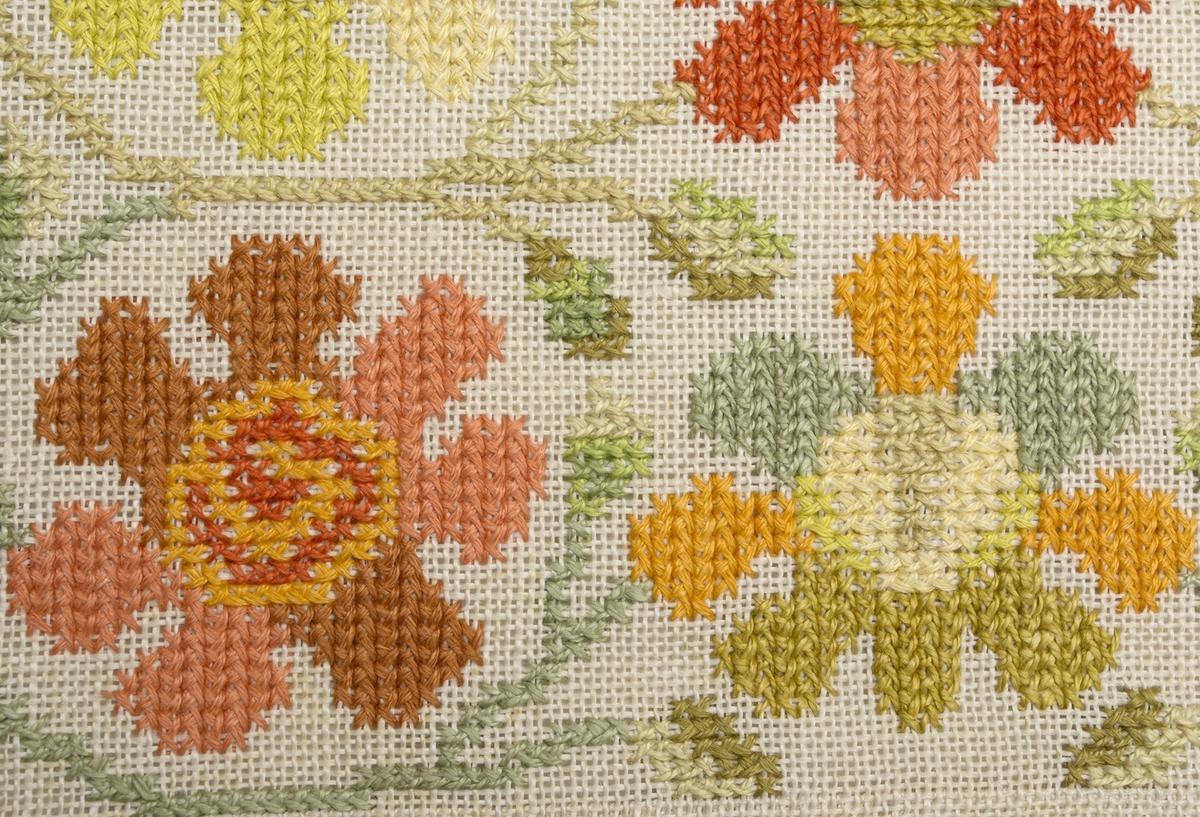 Stoppad kudde. Broderad i tvistsöm på linne. 3x3 blommor i olika nyanser i gult och orange med slingrande bladrankor omkring. Orange linnebakstycke.