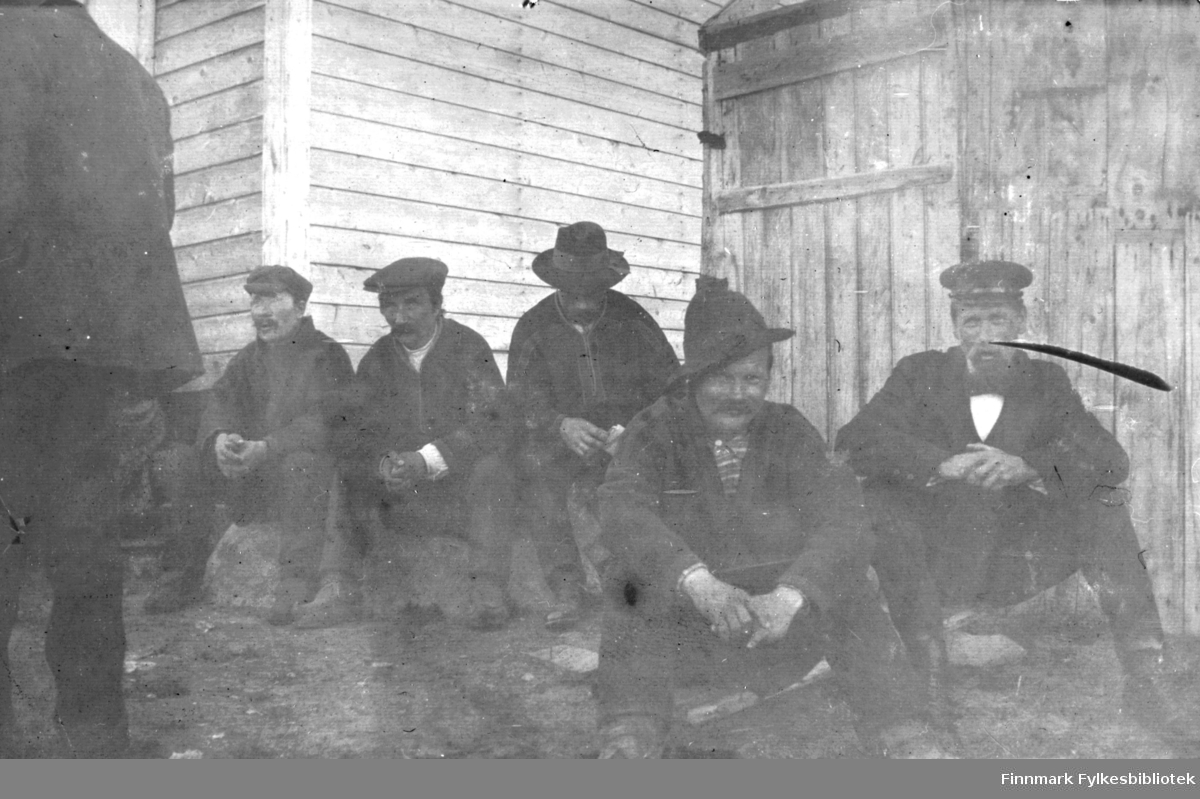 En gruppe menn sitter ved en husvegg, antakelig på Langnes, og kanskje i forbindelse med Langnesmarkedet. De fleste er koftekledde