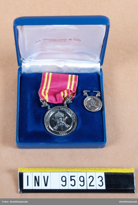 Kronobergs regementes (I 11) minnesmedalj i silver, 8:e storleken, 1997.  Band: rött med två gula ränder på vardera sidan. Bandet är fäst vid en smal stång uppburen av snedställda bladornament.  Medalj och miniatyrmedalj i blå ask klädd med blå sammet och vit siden.