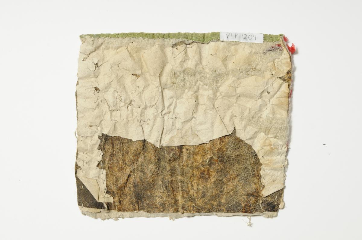 """Bringeduk i raud ull, i to ulike tøy. Nede eit stykke grønn silkebrokade, sydd på lin. Ein """"kniplingsbord"""" med perler påsydd vannrett midt over, ovanfor den ein bord med metallknipling. Smal grønn kant opp. Bakstykke, eit lag pergament, skinn og papir. Også merker etter ulltøy."""