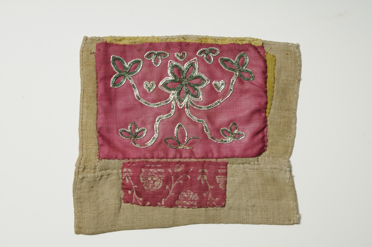 Bringeduk i rosa satengvove ulltøy, påsydde grønne og kvite perler.Kanta oppe med gul silke. Nederst påsett eit rosa ulltøy med kvitt rosemønster. På høgre sida ein liten bit med gult ulltøy.Fòra med ubleikt lin.