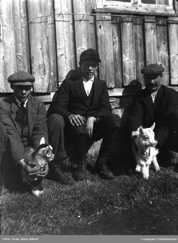 Tre menn med geitekillinger foran en husvegg.