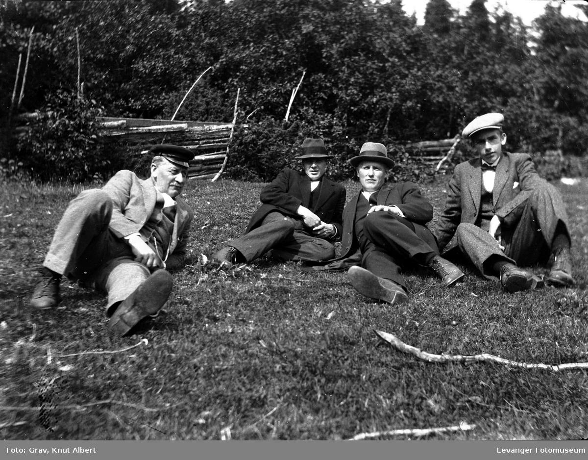Fire menn sitter på marka.