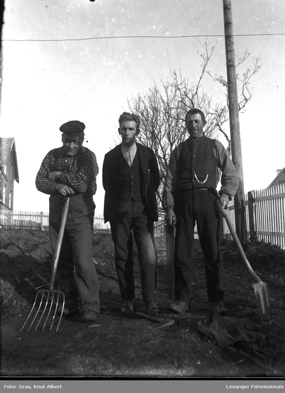 Gruppe, tre menn med redskaper. Nils Grav i midten, Ole Grav til venstre