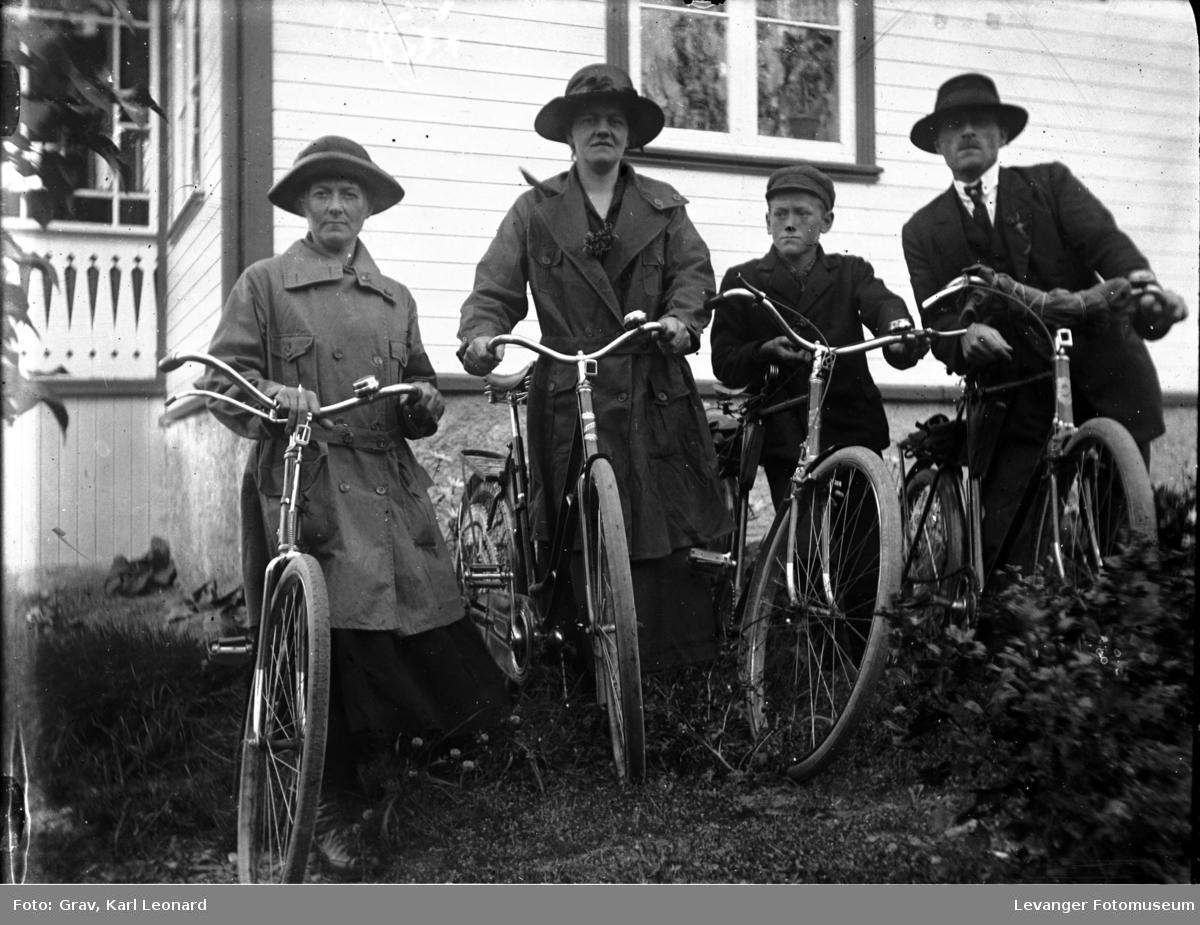 Gruppebilde, familie med sykkel, kan være tatt på losjelokalet på Øvre.