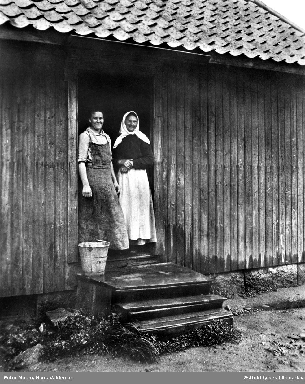 Mor og datter i bryggerhusdøra i Hans Nielsen Haugesvei (Hauge østre), Rolvsøy ved Fredrikstad -  vaskedag, ca. 1915.  Helga Jakobsen f. Moum med langt strieforkle, og hennes mor Ellen Moum.