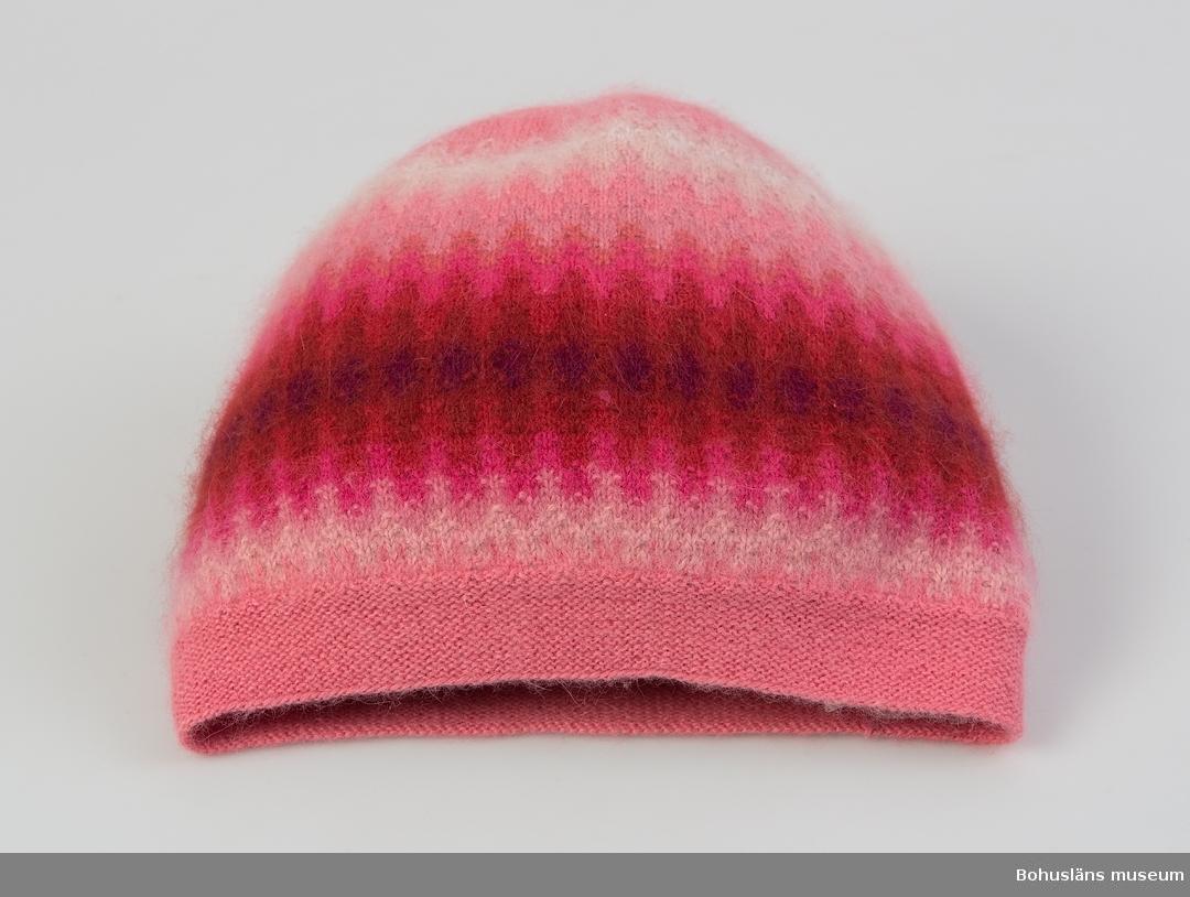 """Mönster Kerstin Olson. Mössa """"Sagopalmen"""" i angora och finull. Fyra olika rosa färger, cerise, tegelfärg, ljusbrunt, blått, beige och vitt. Välbevarad.  Ett mörkt löstagbart innerstöd av syntetmaterial finns. Jfr uppgifter på UM027468."""