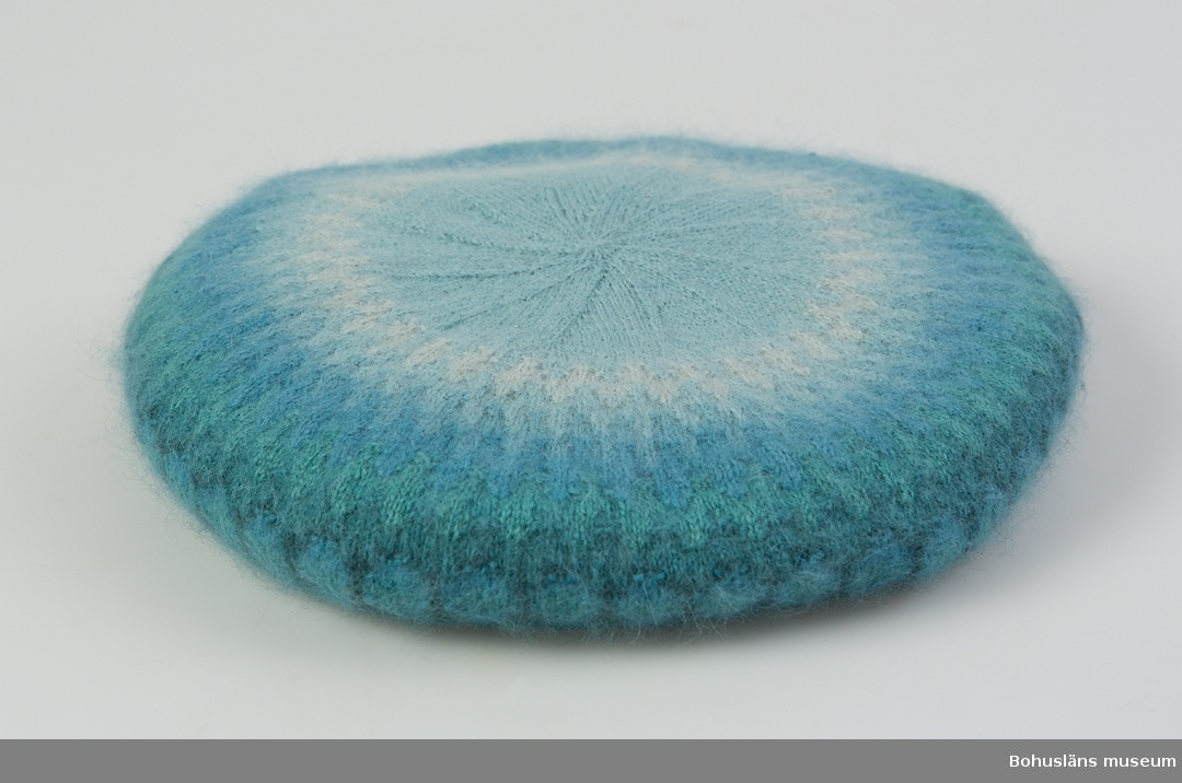 """Barett  i mönster """"Akvamarinen"""", huvudbonad i  ljusblått, gråblått, mellanblått, turkos och svart. Design Kerstin Olson. Välbevarad."""