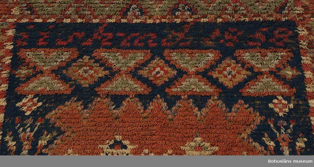 """Täcke, prydnadsrya, troligen bröllopstäcke, vävd med inslagna nockor över hela ytan bildande ett grafiskt komponerat mönster i grönt, rött, blått och vitt med mittspegel och kantbård. Centralmotiv på blå botten föreställande två vita kannor med blå (mannen?) respektive röd (kvinnan?) botten med pip och handtag på en rektangulär uddkantad röd platta, på ömse längsgående sidor omgiven av en högrest blomsterstängel. Ovanför plattan en rad med omväxlande enkla och dubbla trianglar (timglas) i rött, grönt och vitt krönta av svårläst signering och datering, troligen """"iis hmd 1858"""" i röda nockor. Nedanför centralmotivet en rad med upprepade kvadrater och trianglar (timglas) i omväxlande färger och på raden nedanför dessa en rad med rosor av rött och vitt garn på blå botten.  Kring centralmotivet löper en 25 cm bred kantbård med romber på grön botten varannan romb har haft svarta nockor som nu helt är borta. (Se nedan).  Överdelens hörn/yttersta kvadrater är prydda av en stjärna på röd botten. Nederdelens hörnen/yttersta kvadrater är prydda av ett rutmönster av röda och vita kvadrater samt  idag """"nakna"""" kvadrater utan nockor där tidigare svarta nockor suttit. (Se nedan).  Bottenväven består av ofärgat, ljusbrunt entrådigt ullgarn i inslagsrips med varp av lintråd, den översta fjärdedelen av ett mörkare brunt ullgarn. Ryan består huvudsakligen av ullgarnsnockor av en enfärgad, tvåtrådig, ouppklippt ögla och två avklippta  ändar.  I vävnaden finns också andra varianter där bomullsgarn ingår; ett antal nockor består av tvåtrådigt ullgarn och entrådigt bomullsgarn i flera färger, blandade,  ett antal nockor består av entrådigt enfärgat bomullsgarn och dessa  ofta är centralt placerat i motivet samt ett antal  flerfärgade nockor av enbart bomullsgarn. Centralmotivets blå platta omges t. ex. av en bård helt och hållet i bomullsgarn.  De röda och gröna färgerna är växtfärgade, den blå troligen färgad med preussiskt blått med några smärre inslag av indigofärgat blått garn. Den svar"""
