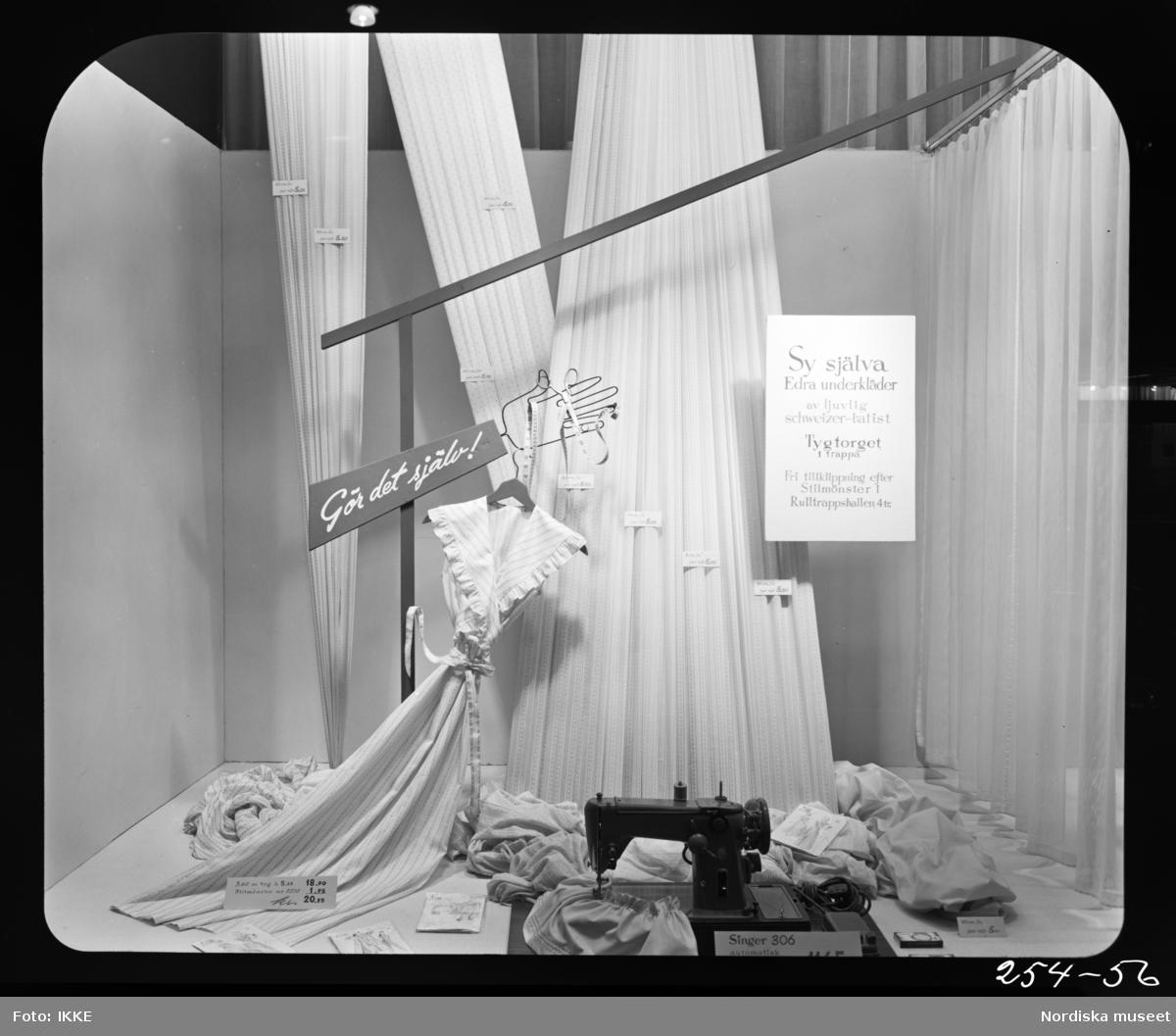 """Skyltfönster på Nordiska Kompaniet. """"Gör det själ, sy själva edra underkläder i ljuvlig Schweizer-batist."""" Textilier, klänning och en symaskin."""