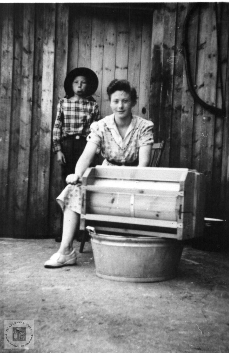 Familien Omdal driver med smørkinning, Øyslebø. Brukerkommentar:  Gutten bak er Leif