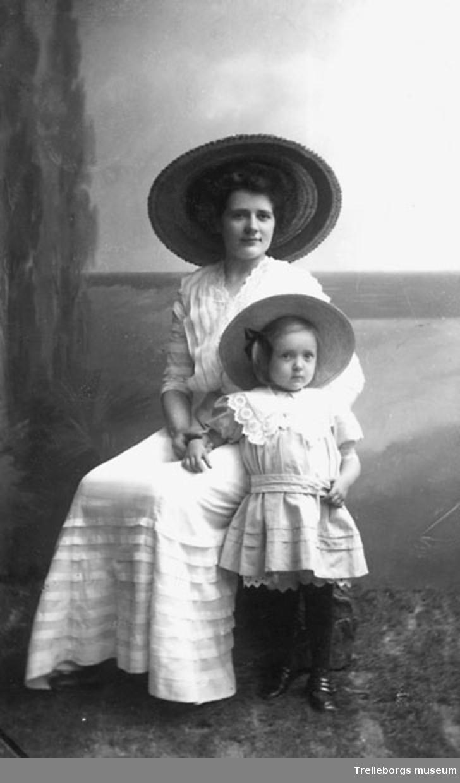 Kvinna med en liten flicka (mor och dotter?) i ljusa sommarklänningar med stora halmhattar.