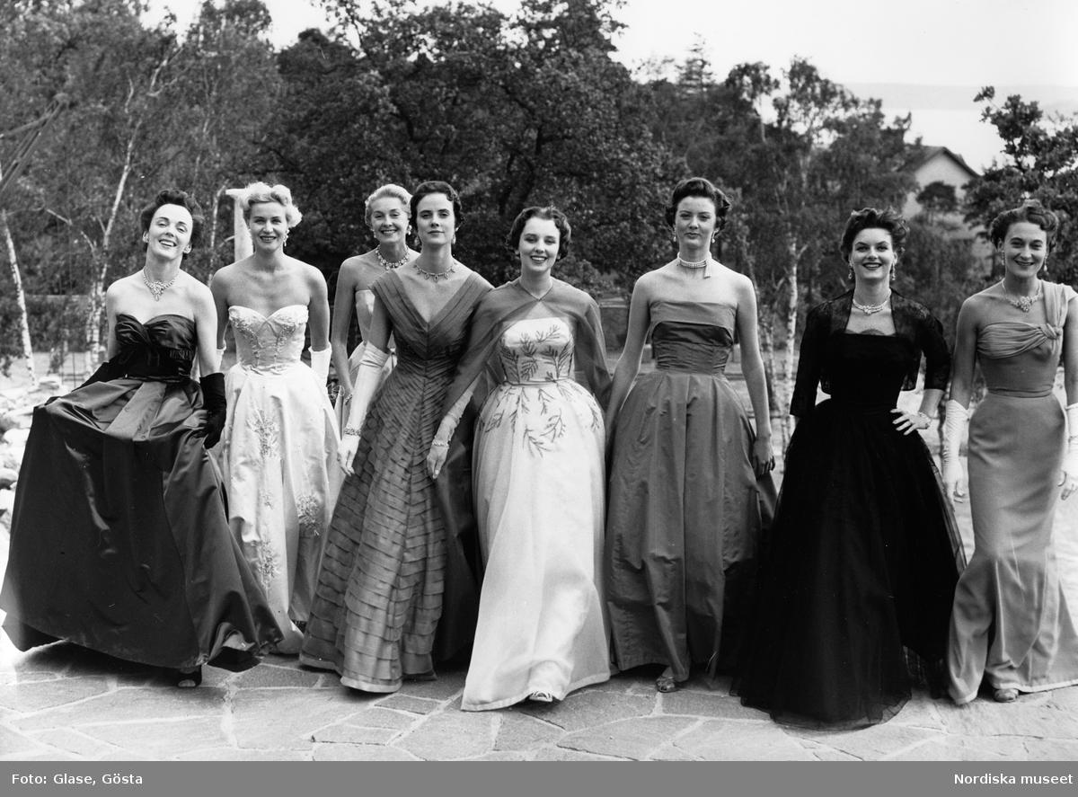 Dammode. Kvinnor i balklänningar på en strand. Aftonhandskar, smycken och en cape.