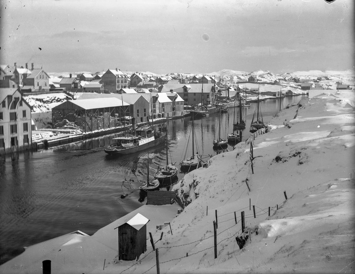 Smedasundet en vinterdag. Dampskip, en færing og noen seilfartøy ankret opp. Sjøhus, trehus og snødekte fjell i bakgrunnen.