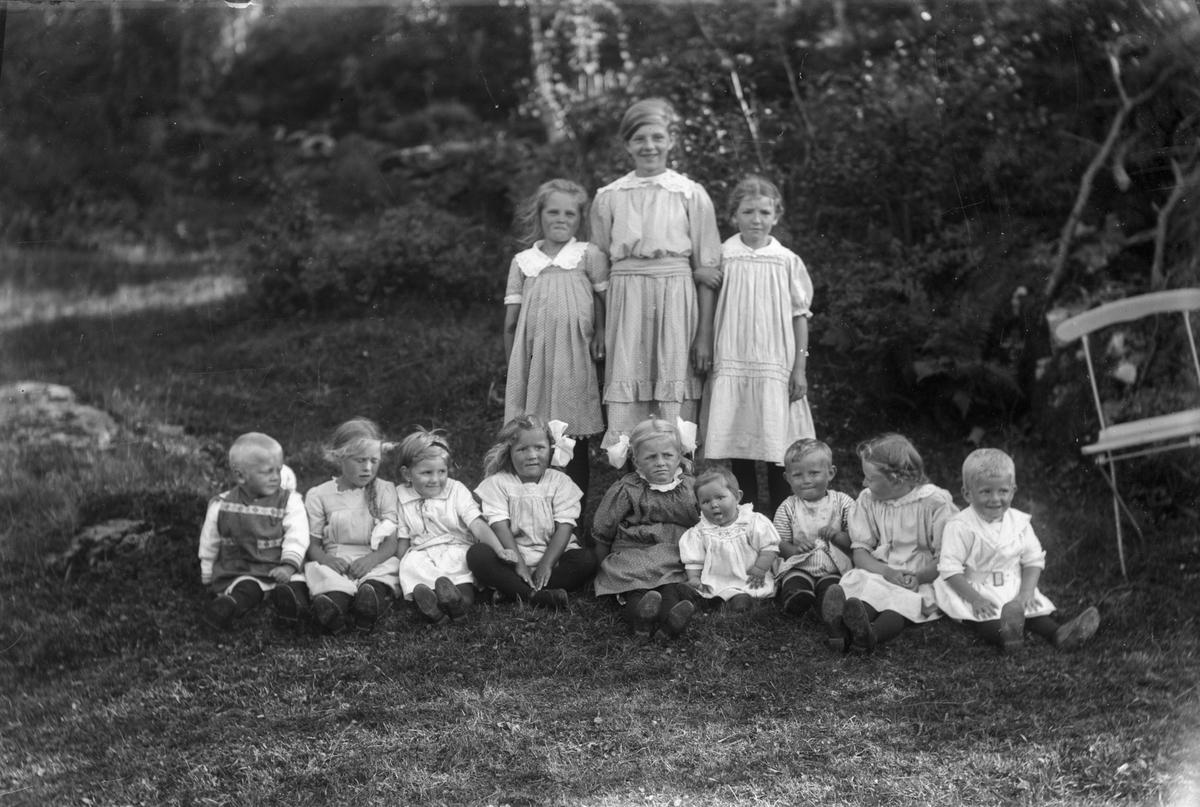 Gruppebilde av 12 barn, hvorav 10 jenter og 2 gutter. Bilde er tatt foran trær. En stol til høyre i bildet.