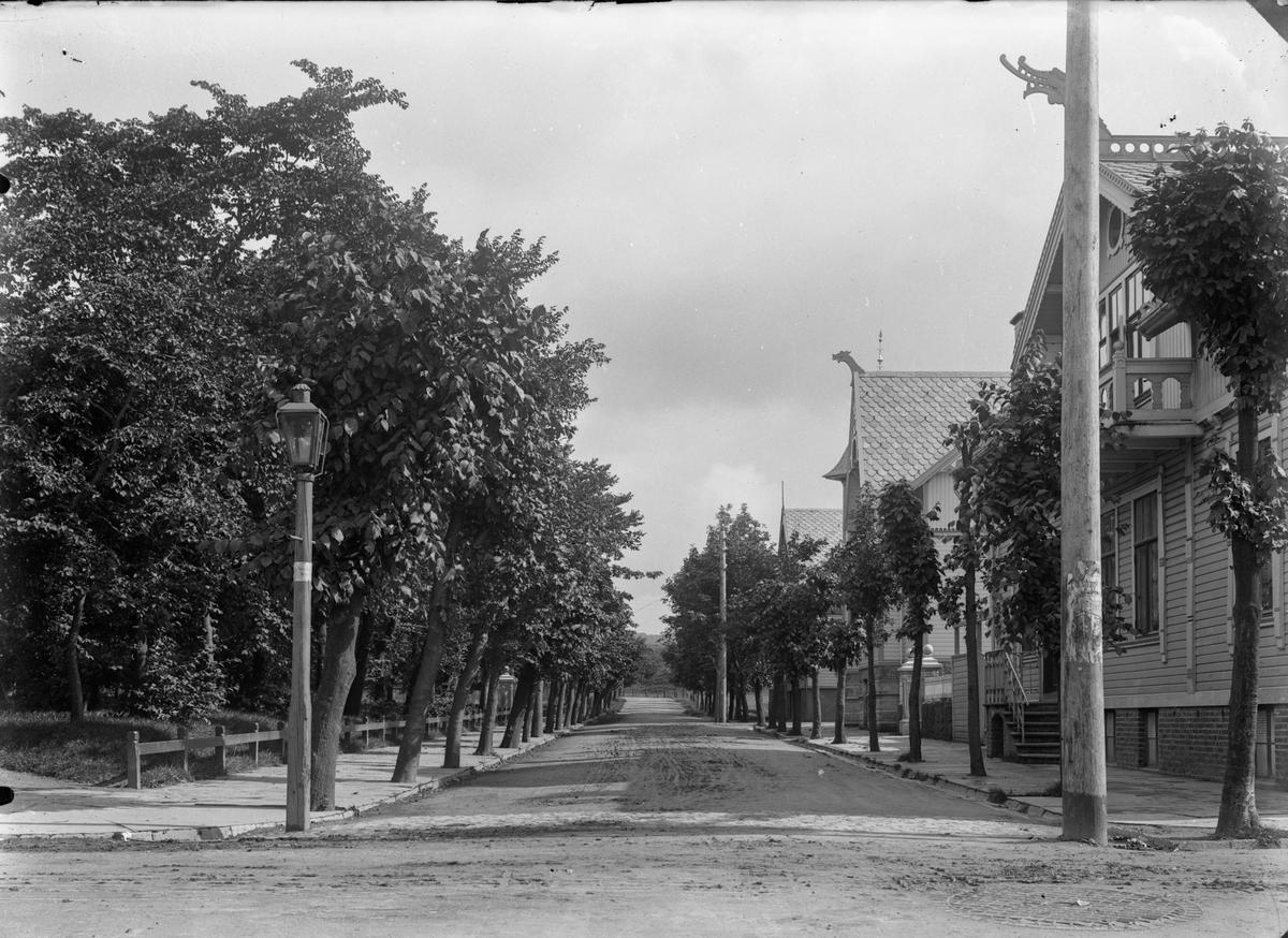 Hjørnet ved byparken. Vei midt på bildet og i forgrunnen. Gatelys. Telefonstolpe. Trær til venstre. Trehus til høyre og i bakgrunnen.