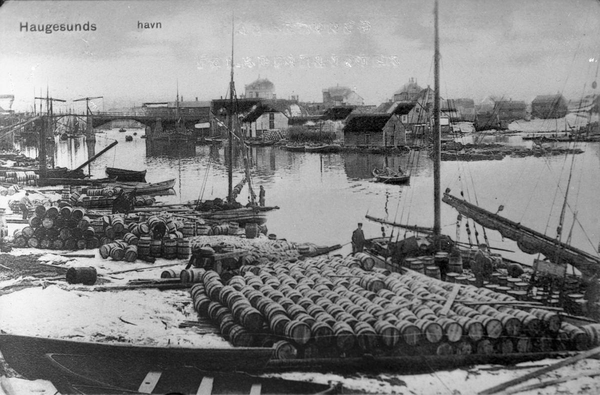 Tønnelager ved Haugesjøen, sett fra nord. Hasseløybroen i bakgrunnen til venstre.  Noen arbeidere. En færing med noen personer ombord midt på bildet. I bakgrunnen ligger Hasseløy med flere sjøhus og trehus. Fiskebåter og seilskuter (?) i bakgrunnen bak Hasseløybroen. Andre færinger ved kai til venstre.