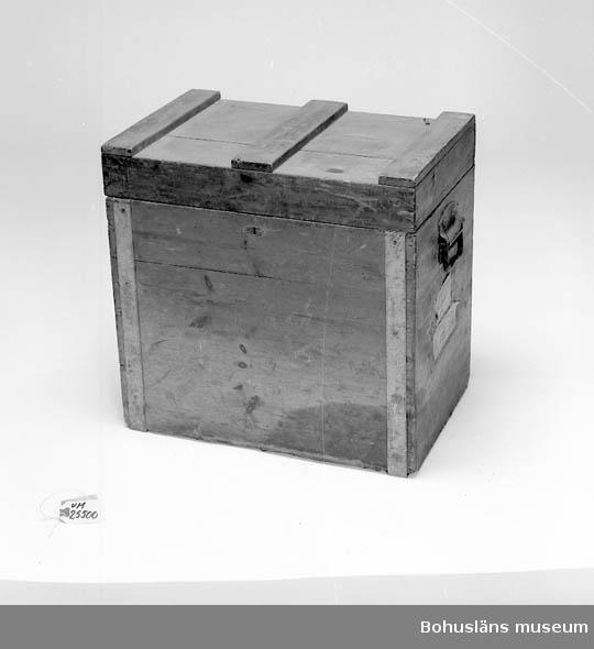 """Skydds- och fraktlåda av trä, (furu) laxade hörn, delvis förstärkta med galvaniserad plåt. På gavlarna järnhandtag fastskruvade. På ena gaveln fastklistrade järnvägsfraktsedlar från Uddevalla och Dingle.  Invändig uppdelad i fack för projektorn och dess tillbehör. Nyckeln till framsidans lås saknas. Handdriven projektor av svartlackerad plåt och järn, fastskruvad på  träplatta av ek. Lins saknas. Skyddshuv av svartlackerad plåt med  prydnadslinjer och tillverkningsfirmans namn i guldfärg. Tre rullar  av svart plåt, varav en med mittrulle i trä.  På insidan av trälådans lock inklistrad instruktionsblankett.  I trälådan förvaras plåthylsa, ursprungligen för """"Colgate & Co.  Shawing stick. New York, USA"""". men här använd för förvaring av apoteksflaska med aceton."""