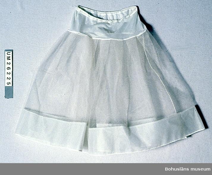 """Vit underkjol av nylonnät. Nedtill ca 11 cm bred fåll  av styvt polyamidtyg. Upptill 12 cm brett parti av mjukt polyamidmaterial. Resårband i kanal i midjan. Sömmarna kantade med bomullsband. I slutet av 1950-talet och början av 1960-talet var det mycket modernt med riktigt stor vidd både i klänningar och i kjolar, särskilt bland tonårsflickor och unga kvinnor. Ett antal olika typer av underkjolar användes, särskilt bomullsunderkjolar som hårdstärktes så mycket som gick i """"Gårda stärkelse"""" eller potatismjöl. Det förekom även skumgummiunderkjolar med stålråd nertill av samma anledning. Denna underkjol torde ha varit mycket modern och litet mer påkostad. Lämnades in till och var med på Bohusläns museums plastutställning december 1995 - april 1996."""
