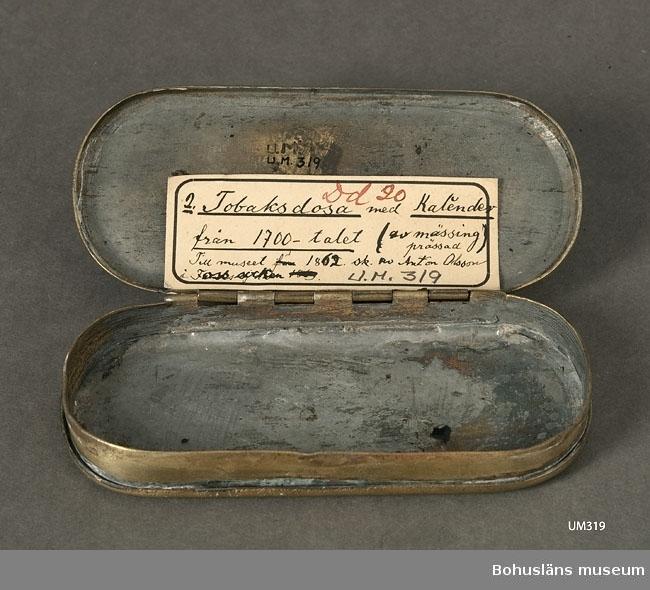 Ur handskrivna katalogen 1957-1958: Tobaksdosa Bottenmått. 13 x 5,5 H: 2,0 Mässing. Lock o botten: kalender Föremålet helt.  Lappkatalog: 95