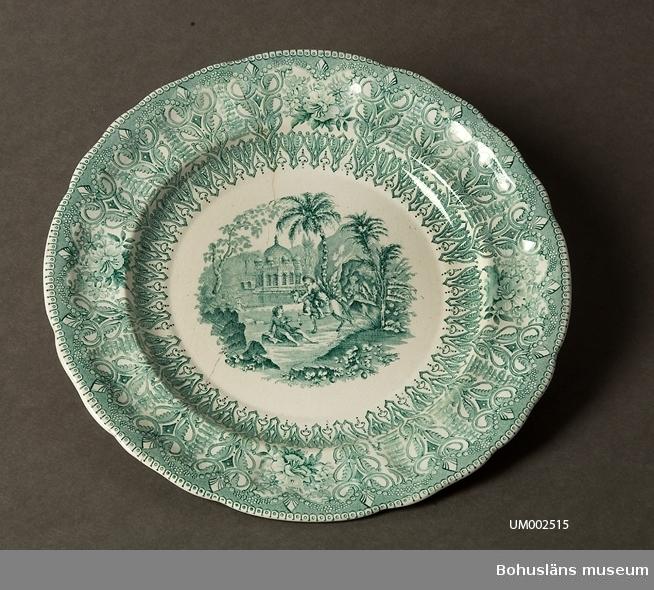 Ur handskrivna katalogen 1957-1958: Grön tallrik m. kinamönster Diam.: 24. Vitt porslin med mönster i grönt. Lagad.  Lappkatalog: 62