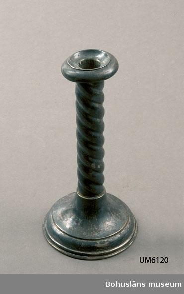 Ur handskrivna katalogen 1957-1958: Ljusstake i form av vriden kolonn H.: 20,7 cm. Fotens diamet.: 10,3 cm. Föremålet helt.  Lappkatalog: 90